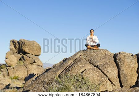 Hispanic woman practicing yoga on rock