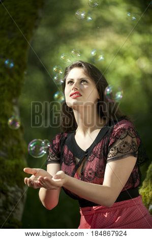 Caucasian woman trying to catch bubbles in her hands