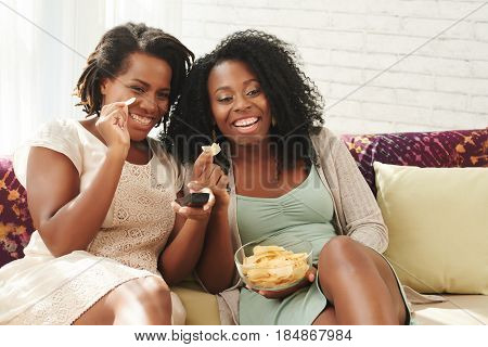 Female friends eating potato chips and watching tv show