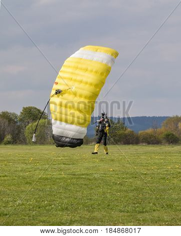 PRIBRAM CZECH - APRIL 30 2017. Parachutist with a yellow parachute landed on the grass. Skydiver in a black overalls with glasses landing with a parachute.