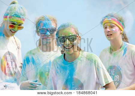 STOCKHOLM SWEDEN - MAY 22 2016: Four smiling teenager and glasses covered with color dustin the Color Run Event in Sweden May 22 2016