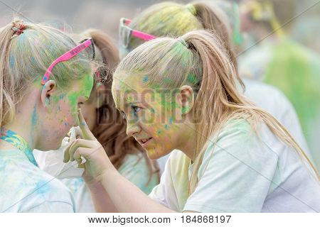 STOCKHOLM SWEDEN - MAY 22 2016: Two teenage girls covered with colorful color dust helping each others makeup in the Color Run Event in Sweden May 22 2016