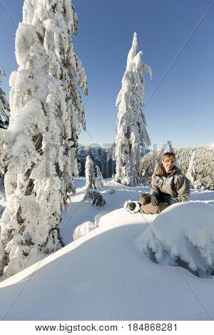 Caucasian woman snowshoeing in remote area taking break