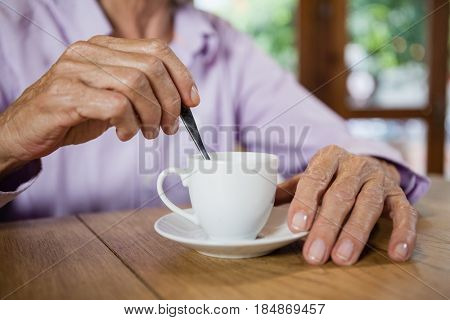 Midsection of senior woman stirring coffee while sitting at table in cafe