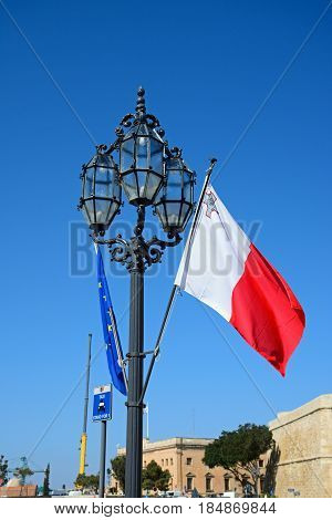 VALLETTA, MALTA - MARCH 30, 2017 - Wrought iron streetlight with the Maltese flag and European Union flag in Castille Square Valletta Malta Europe, March 30, 2017.
