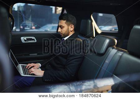 Side view portrait of handsome Middle-Eastern businessman using laptop on backseat inside expensive car