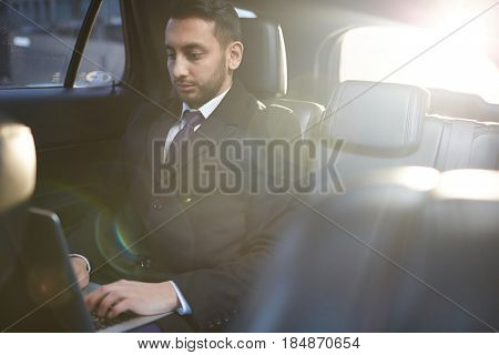 Sunlit portrait of handsome Middle-Eastern businessman using laptop on backseat inside expensive car