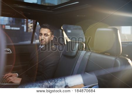Portrait of handsome Middle-Eastern businessman on backseat in expensive car and looking at camera