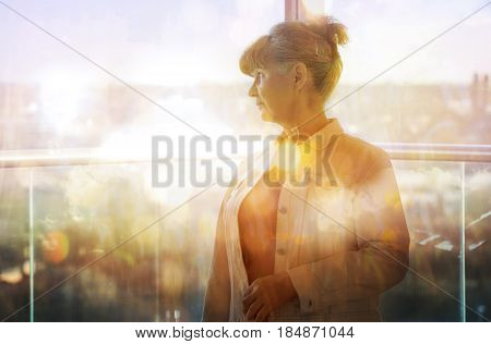Pension age good looking woman against of window and city view.
