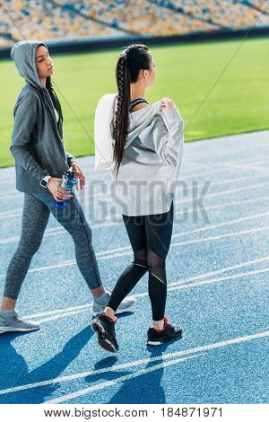 Two Young Sportswomen Walking Together On Running Track Stadium