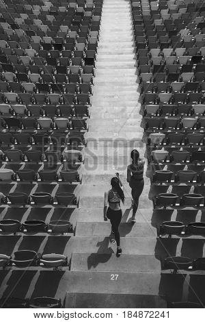 Two Sportswomen Running On Stadium Stairs, Black And White, Running Women Concept