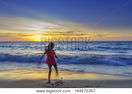 Motion blurred Silhouette little girl on the beach at sunse