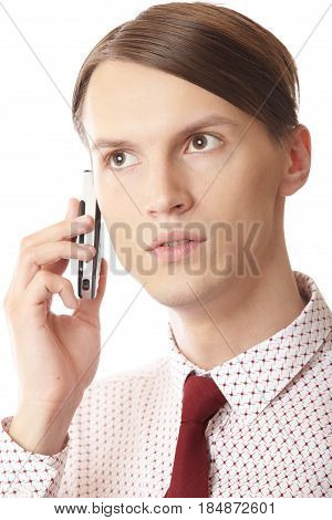 Serious businessman talking via cell phone on a white background