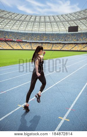 Back View Of Young Fitness Woman In Sportswear Sprinting On Running Track Stadium