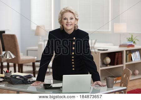Caucasian businesswoman leaning on desk