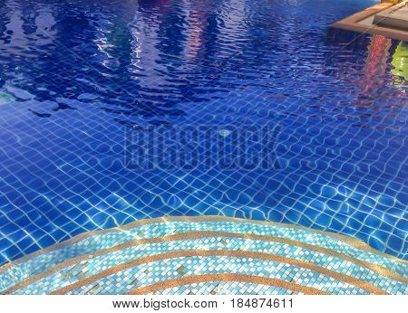 Staircase mosaic in to clear blue swiming pool sun glare