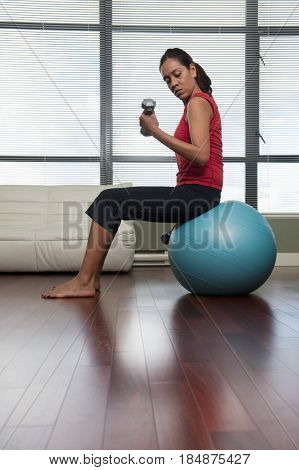 Hispanic woman exercising with hand weights