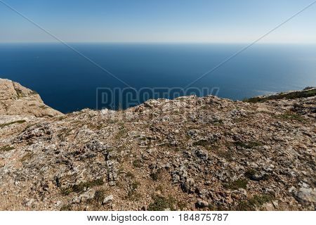 Mountain ledge with sea and horizon on background for product placement. Rock edge and steep with blue water on background for designers needs