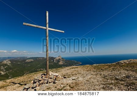 Christian wooden cross on mountain top, rocky summit, beautiful inspirational landscape with ocean, clouds and blue sky, looking at scenic blue sea and white clouds outdoors