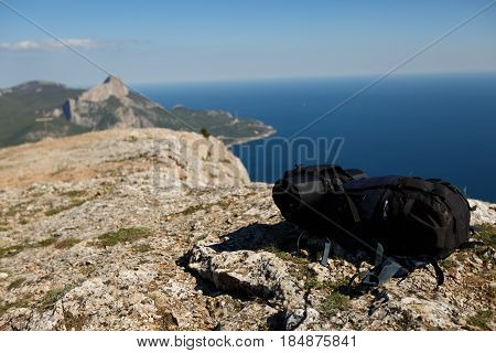 Backpack on peak of mountain with sea and mountains on background, healthy lifestile and hiking concept. No people. Lot of copy space