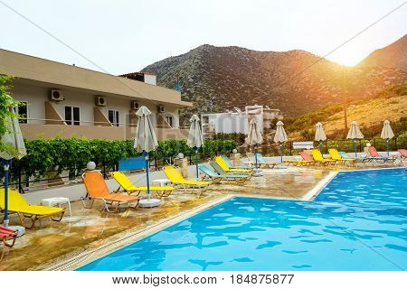Relax and sunbathe by pool with clear blue water in Resort hotel Atali Village 4 star. Empty pool without tourists early morning at hotel. Bali Rethymno Crete Greece