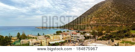 Bali Greece - May 2 2016: View from top of hotel Atali Village on Greek architecture of resort town Bali coast of Livadi Beach and high mountain. Cloudy day on Cretan sea in tourist season. Crete