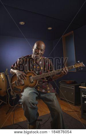 African American man playing guitar in studio