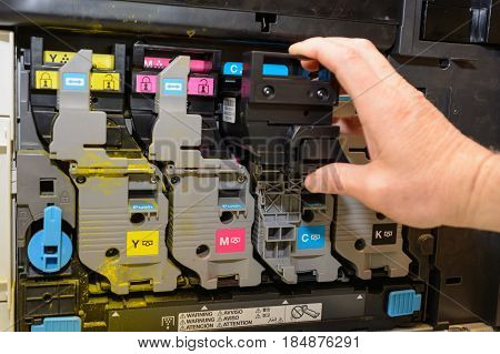 Person exchanging color cartridge with laser printer - close-up