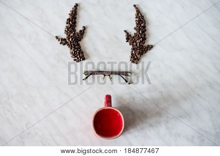 Deer. Horns from coffee beans. Glasses. Red cup