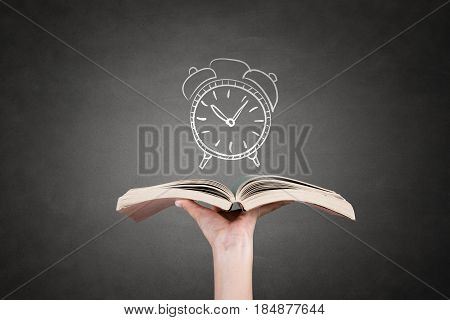 Human hand holding book with clock. Concept of time management