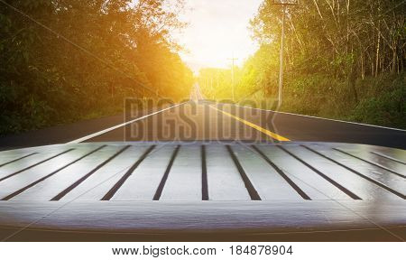Blurred of road to the nature at sunset time with wooden tabletop use for products display