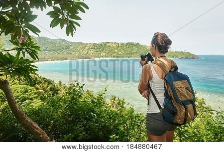 Purposeful tourist with backpack enjoying sunny coast view. Traveling along mountains and coast freedom and active lifestyle concept.