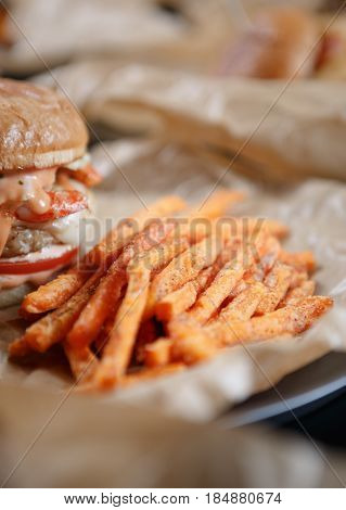 Big tasty burger with sauceburned cheese & meat served with fried carrot sticks on brown crafted paper in fast food restaurant.Fat unhealthy junk food menu in cafe.Close up
