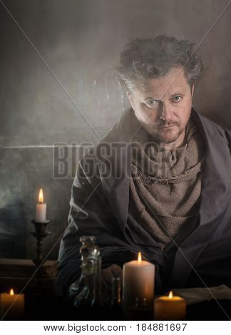 portrait of a sorcerer with candles indoor