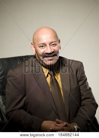 Hispanic businessman sitting in chair