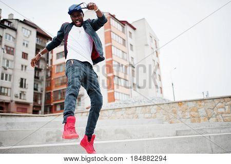 Portrait Of Jumping Stylish African American Man On Sportswear, Cap And Glasses. Black Men Emotion M