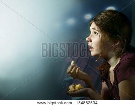 teenager girl watching horror movie with pop corn in cinema