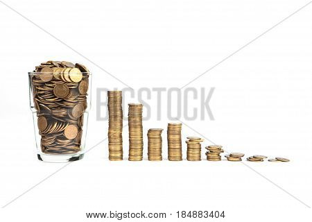 glass of coins and decreasing stacks on white background