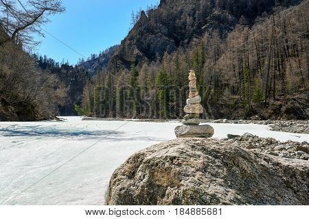 Pyramid of stones on large boulder. White Irkut River