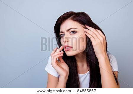 Close Up Portrait Of Troubled Young Girl Touching Lips Looking At Her Skin