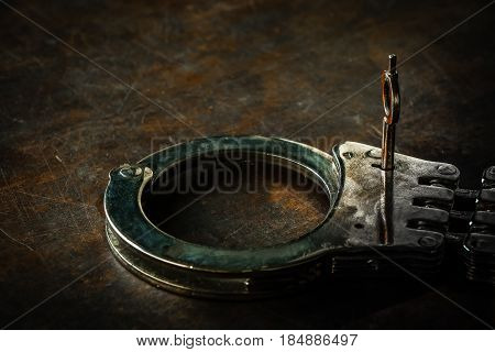Rustic handcuff put on police wooden table