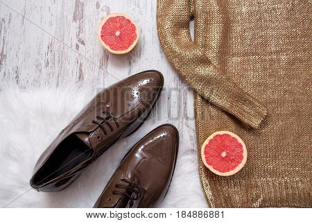 Part Of A Golden Sweater, Brown Patent Leather Shoes And Grapefruit, Wooden Background. Fashionable