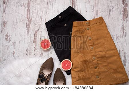 Brown And Black Suede Skirt, Brown Suede Shoes, Cut Grapefruit Halves. Wooden Background. Fashion Co