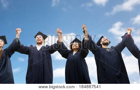 education, graduation and people concept - group of happy international students in mortar boards and bachelor gowns celebrating success over blue sky and clouds background
