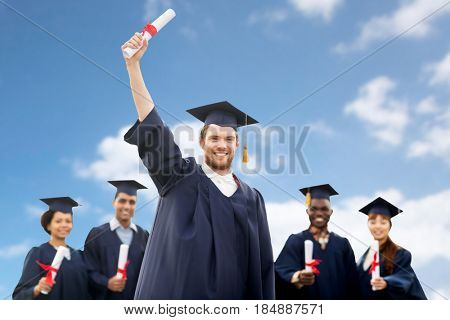education, graduation and people concept - group of happy international students in mortar boards and bachelor gowns with diplomas over blue sky and clouds background