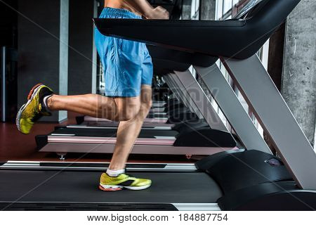 Legs running on the treadmill close up. A muscular man in yellow sneakers and blue shorts running down the treadmill in the gym