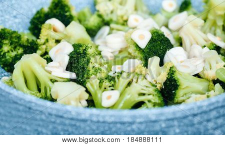 broccoli in a blue plate. Braised broccoli with garlic.