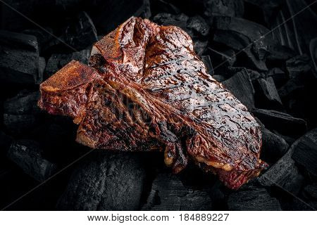 Grilling a tasty tender marinated t-bone steak on a coals. Close up view.