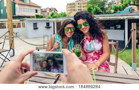 Man hands taking photo with smartphone to two happy young women with sunglasses holding green vegetable smoothies outdoors