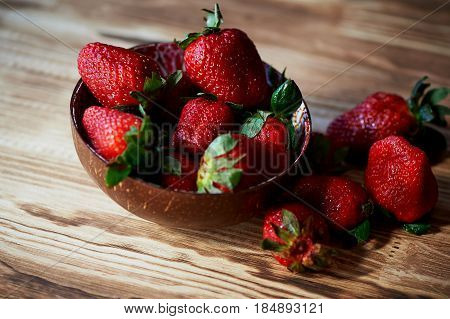 Red juicy strawberry on a wooden background, in a wooden bowl. Bowl from coconut.Tasty